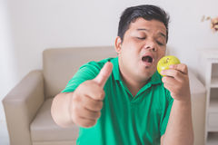 Obese man trying to eat healthy fresh food Stock Images