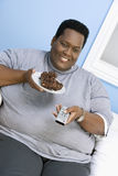 Obese Man Watching Television. While holding plate of pastry Stock Photos