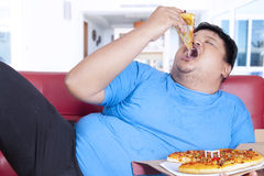 Obese person bite a slice of pizza. Obese person eats pizza while sitting on couch at home Royalty Free Stock Photos