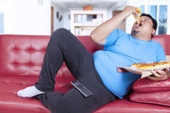 Obese person bite a slice of pizza 1 Royalty Free Stock Photo