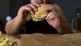Obese person biting big burger, addicted to unhealthy junk food, overeating stock images