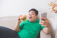 Obese person eating hamburger while using mobile phone Royalty Free Stock Photos