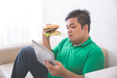 Obese person eating hamburger while using tablet pc Royalty Free Stock Photo