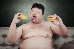 Obese person eats cheeseburger on sofa. Photo of a young obese man sitting on the sofa while eating two cheeseburgers Royalty Free Stock Photography