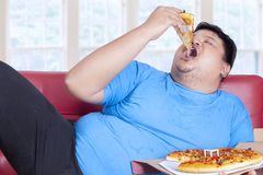Obese person eats pizza 1. Obese person eats pizza while sitting on couch at home Stock Images