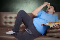 Obese person eats pizza 3. Obese person eats pizza while sitting on couch at home Royalty Free Stock Photography