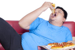 Obese person eats pizza 2. Obese person eats pizza while sitting on couch at home Royalty Free Stock Photography