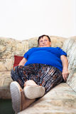 Obese retired woman. Portrait of obese elderly woman lying on sofa Royalty Free Stock Photography