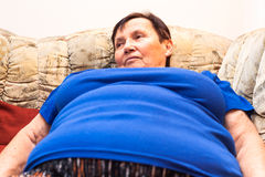 Obese senior woman. Close up of obese senior woman lying on sofa Stock Photo