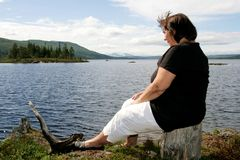 Obese woman. Sitting by a lake Royalty Free Stock Photo