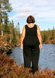 Obese woman. Standing by a tarn Stock Photography