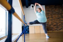 Obese Woman in Ballet Class. Full length portrait of graceful obese woman stretching legs in ballet class by window, copy space Stock Photography