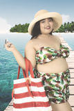 Obese woman with bikini on jetty. Summer holiday concept. Happy overweight woman standing on a wooden jetty while wearing bikini, hat, and carrying a summer bag Royalty Free Stock Photo