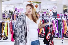 Obese woman carrying much dress in the boutique. Image of obese woman looks happy while carrying much dress in the boutique royalty free stock images