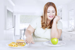 Obese woman chooses healthy food Stock Photo