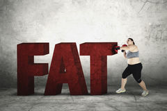 Obese woman crushing fat word. Portrait of an obese woman wearing boxing gloves to crushing word of fat Stock Photography