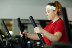Obese Woman Determined to Lose Weight in Gym. Side view portrait of determined overweight woman working out in gym: using ellipse machine with effort to lose Stock Images