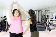 Obese woman doing exercise with trainer. Obese women doing exercise with her personal trainer in the fitness center Stock Photo