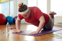Obese Woman Doing Push Up Exercises to lose Weight. Portrait of young obese woman working out on yoga mat in sunlit fitness studio: performing knee push up Royalty Free Stock Images