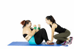 Obese woman doing sit up with instructor. Obese women doing sit up on the mat helped by her instructor, isolated on white background Stock Photos