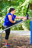 Obese woman doing sport stretching outdoors in park Stock Photo