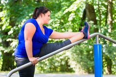 Obese woman doing sport stretching outdoors in park. In summer Royalty Free Stock Photo