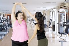 Obese woman doing a workout with her instructor. Picture of female instructor helping obese women to exercising while standing in the gym center Stock Photography