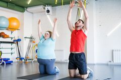 Obese Woman Doing Yoga. Full length portrait of obese young women doing fitness exercises in gym with personal trainer helping her, copy space Stock Photos