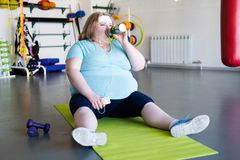 Obese Woman Drinking Water after Workout. Full length portrait of tired obese woman sitting on yoga mat and drinking water after fitness training in gym Stock Photography