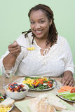 An Obese Woman Eating Food. Portrait of a happy obese African American woman having food at home Royalty Free Stock Photography