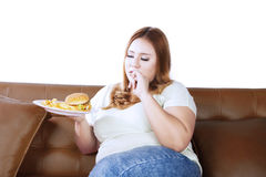 Obese woman eating a junk food Royalty Free Stock Photo