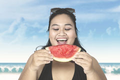 Obese woman eating watermelon on beach. Obese woman wearing swimsuit, eating fresh watermelon on the beach Stock Photo