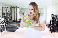 Obese woman eats measuring tapes. Portrait of obese woman eats measuring tapes on bowl while standing in fitness center Stock Images
