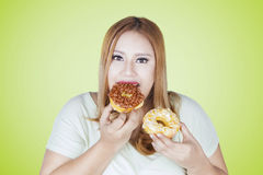Obese woman eats two donuts. Portrait of obese woman eats two donuts in her hands while looking at camera Stock Images