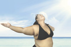 Obese woman enjoying holiday on beach. Obese woman enjoying her holiday on the beach while standing under sunlight Stock Image