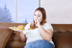 Obese woman enjoying junk food at home Stock Photo