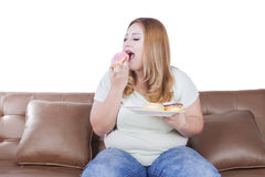 Obese woman enjoys donuts Royalty Free Stock Photo