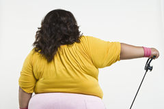 An Obese Woman Exercising. Rear view of an obese woman exercising isolated over white background Stock Images