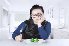 Obese woman feeling bored with broccoli Stock Photos