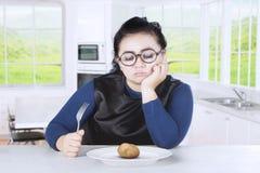 Obese woman feeling bored with potato Stock Photos