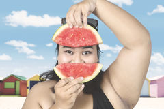 Obese woman with fresh watermelon. Obese woman wearing swimsuit with slice of fresh watermelon near the cottage Royalty Free Stock Photo