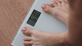 Obese woman getting on scales for weight control during healthy diet, weightloss stock video