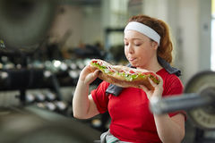 Obese Woman Giving in To Food Temptation in Gym Royalty Free Stock Photography