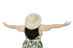 Obese woman with hat and bikini. Rear view of obese woman standing in the studio while wearing swimsuit and a straw hat. Summer concept Royalty Free Stock Photography