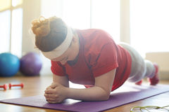 Obese Woman Holding Plank Exercise in Fitness Studio. Portrait of young obese woman working out on yoga mat in sunlit fitness studio: holding plank exercise with Royalty Free Stock Images