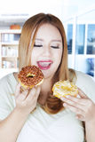 Obese woman holding two donuts. Portrait of obese woman holding two donuts while standing at home Stock Photos