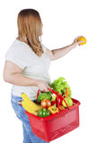Obese woman holds fresh orange. Obese woman holding fresh orange while carrying vegetable on shopping cart, isolated on white background Stock Image