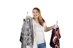 Obese woman holds many clothes. Portrait of happy obese woman holding many clothes and smiling at the camera, isolated on white background Stock Photography