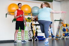 Obese Woman Jumping Rope. Full length portrait of obese women jumping with rope in gym while training with fitness instructor, copy space Royalty Free Stock Photo