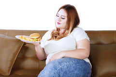 Obese woman with junk food on couch Stock Images